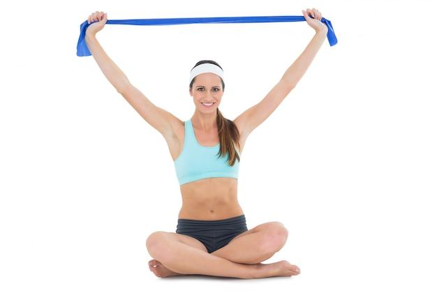 Fit jonge vrouw te oefenen met een blauwe yoga riem