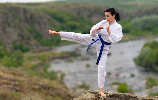 Fit jonge vrouw training in kickboksen buiten op een rots