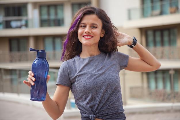 Fit kaukasisch meisje met blauwe fles in haar hand die buiten staat doen oefeningen concept