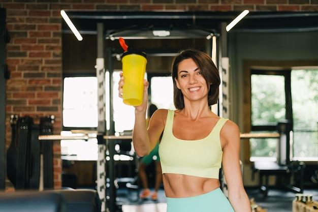 Fit kaukasische mooie vrouw in het passen van sportkleding op sportschool houdt eiwit shaker