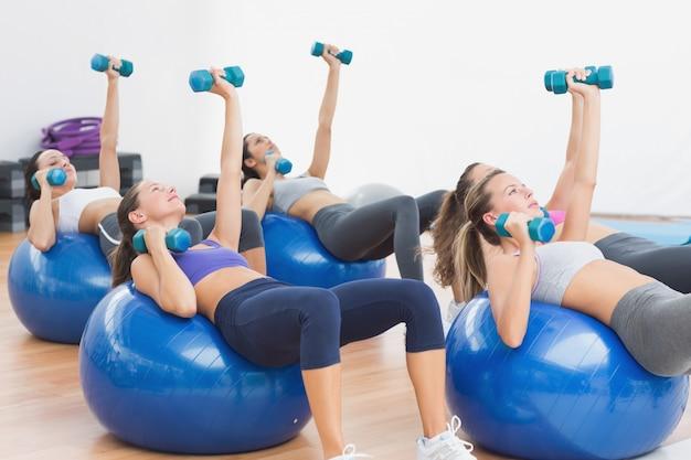 Fit klasse trainen met halters op fitness ballen