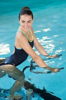 Fit lachende vrouw fietsen op aquafiets in zwembad