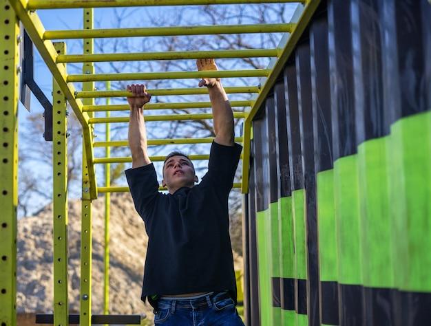 Fit man cross-training op apenstangen. fitnesstraining op brachiatieladder in een buitengymnastiek buiten. mannelijke atleet die op horizontale staven zwaait