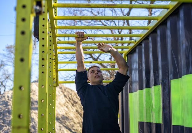 Fit man cross-training op apenstangen fitnesstraining op brachiatieladder in een openluchtgymnastiek