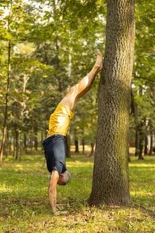 Fit man die alleen yoga beoefent in het bos