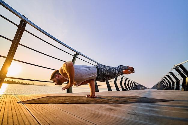 Fit man die één handstand doet terwijl hij alleen yoga beoefent in de buurt van de oceaan