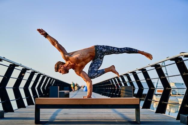 Fit man die met één hand staat terwijl hij alleen yoga beoefent in de buurt van de oceaan tegen de lucht in de schemering of zonsopgang