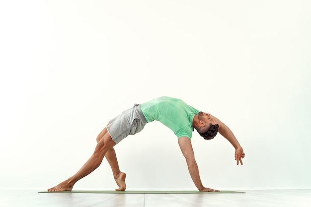 Fit man die yoga beoefent, stelt camatkarasana tegen witte muur against