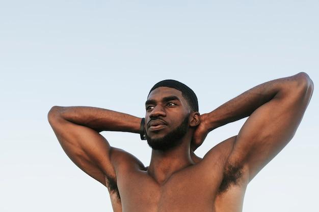 Fit man die zich uitstrekt op het strand