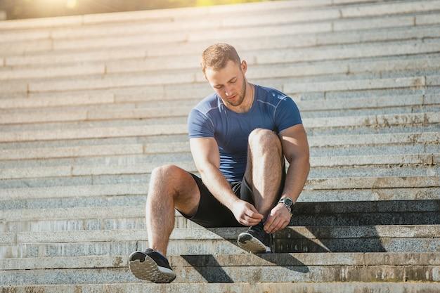 Fit man doen oefeningen buiten in het park