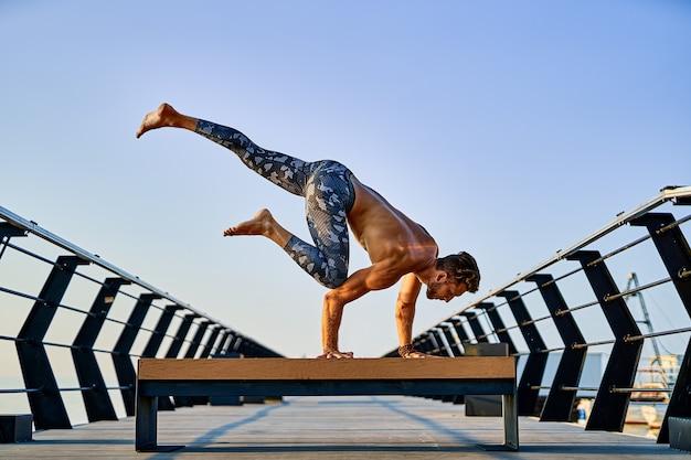 Fit man doet een handstand terwijl hij alleen yoga beoefent in de buurt van de oceaan tegen de lucht in de schemering of zonsopgang