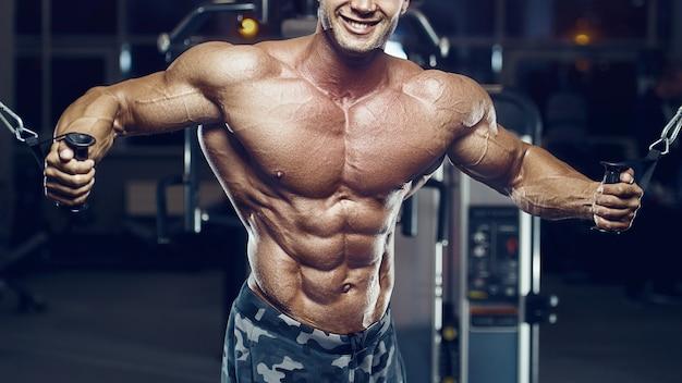 Fit man doet kabelovergang. borstspieren trainen in de sportschool. borstoefening oppompen