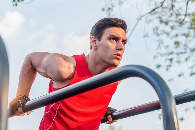 Fit man doet triceps dips op parallelle staven bij park buitenshuis te oefenen