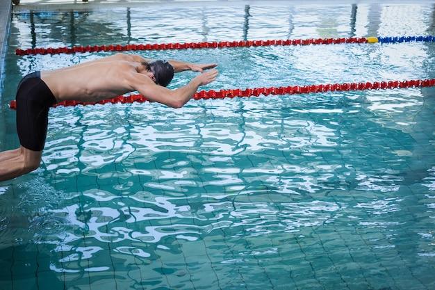 Fit man duiken in het water bij het zwembad