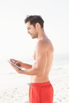 Fit man met behulp van tablet op het strand