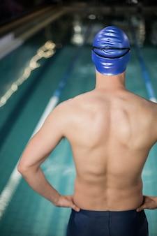 Fit man met de handen op de heupen bij het zwembad