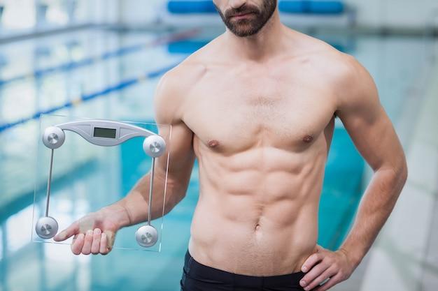 Fit man met een wegingsschaal bij het zwembad
