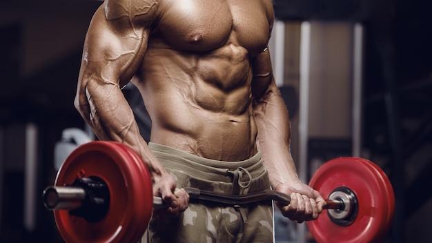 Fit man opleiding armspieren op sportschool. biceps-oefening oppompen.