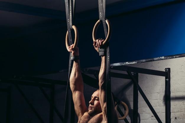 Fit man optrekken op gymnastische ringen.