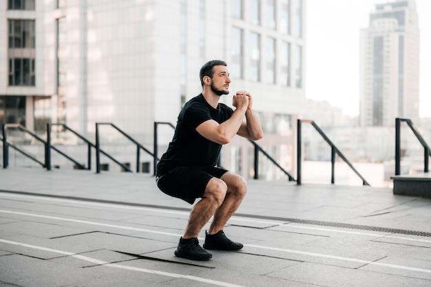 Fit man training lucht squat oefening. fit man die buiten crossfit traint. jonge knappe kaukasische mannelijke fitness model en instructeur buitenshuis. zwarte sportkleding. sport in grote stad concept.