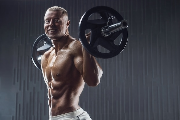 Fit man training spieren op sportschool op donkere achtergrond