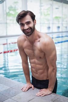 Fit man uit het water bij het zwembad