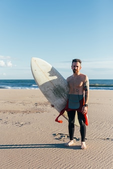 Fit man van middelbare leeftijd met surfplank op leeg strand op warme zomerdag