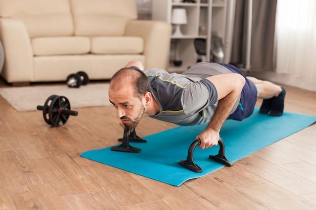 Fit man verhoogt zijn borststerkte door push-ups te doen tijdens de wereldwijde pandemie.