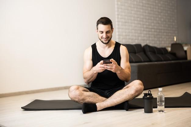 Fit man zit op yogamat met gekruiste benen en sms't met vrienden via de telefoon. rust tijd. atletische man is lui om zijn training thuis te doen en leest grappige memes online.