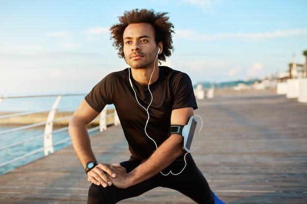 Fit mannelijke afro-amerikaanse jogger met borstelige kapsel zijn spieren opwarmen voordat hij gaat hardlopen. man atleet in zwarte sportkleding benen strekken met stretch oefening op houten pier met witte koptelefoon op.