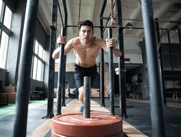 Fit mannelijke atleet doet oefeningen in de sportschool.