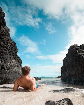 Fit mannelijke leggen en ontspannen op het zandstrand in de buurt van grote zwarte rotsen en kijken naar de zee