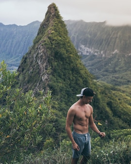 Fit mannelijke wandelaar in een zwart-wit pet staande in het midden van grasvelden in hawaï