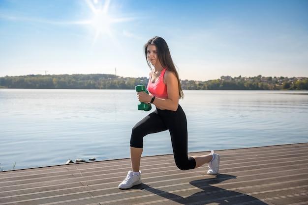 Fit meisje doet oefening met halters in haar handen in de natuur, vlakbij het meer