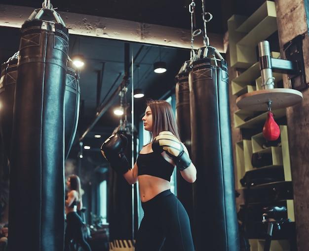 Fit meisje in sportkleding en bokshandschoenen treinen blazen tegen een bokszak in een donkere sportschool