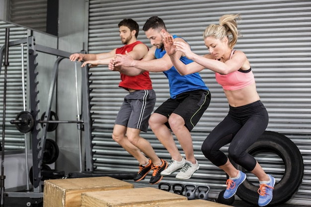 Fit mensen doen oefeningen met doos op crossfit sportschool