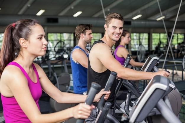 Fit mensen op elliptische fiets op sportschool