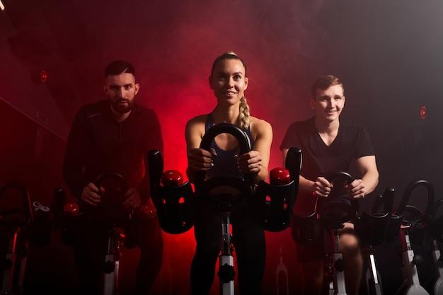 Fit mensen rijden op hometrainers in de sportschool, genieten van trainingstijd, in rokerige rode neonruimte