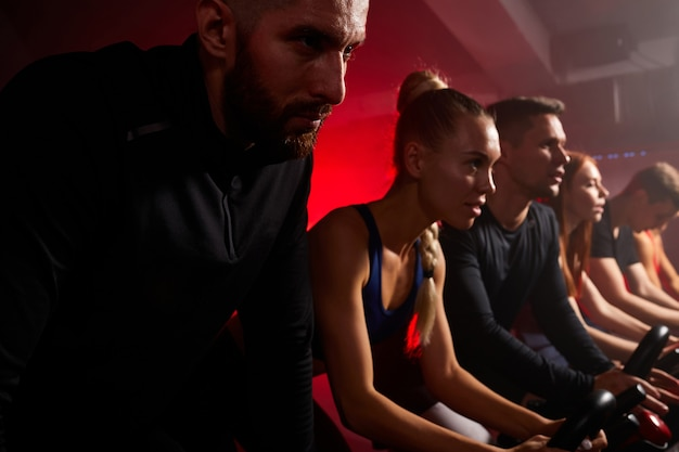 Fit mensen samen op stationaire fietsen tijdens een cardiotraining in de sportschool, geconcentreerd op training die vooruitkijkt