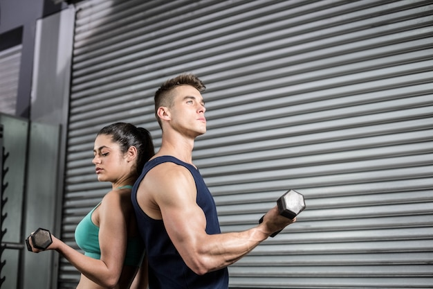 Fit mensen tillen dumbbells rug aan rug op crossfit sportschool