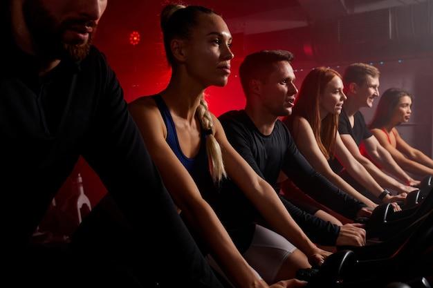 Fit mensen trainen en trainen in de sportschool, fietsen op de fiets van de machine, trainingspak dragen. training, gezond, wellness in fitness