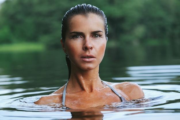 Fit model in grijze bikini in het meer