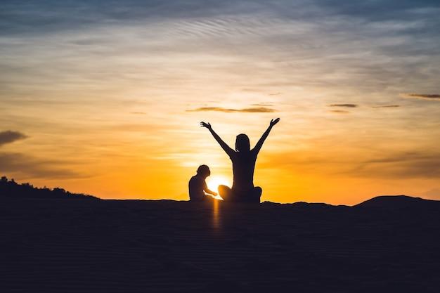 Fit moeder met zoon rennen in de woestijn in gran canaria, maspalomas op zonsondergang.