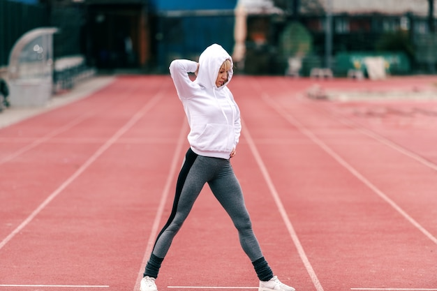 Fit mooie sportieve vrouw met hoodie bij het doen van opwarmingsoefeningen op het circuit. volledige lengte.