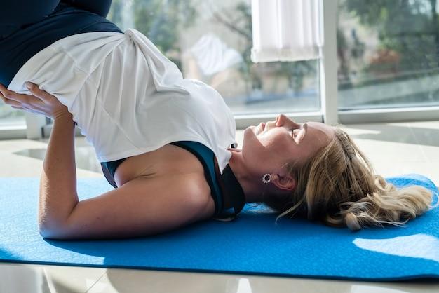 Fit mooie vrouw doet yoga alleen, flexibele lichaamsrek voor gezondheid terug. gezondheidszorg concept.
