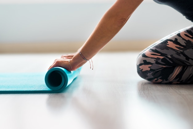 Fit mooie vrouw rollende fitness, pilates of yogamat voor of na het trainen voor het raam in yogastudio club of thuis. benen en lichaam van dichtbij bekijken. gezonde hobby, welzijn