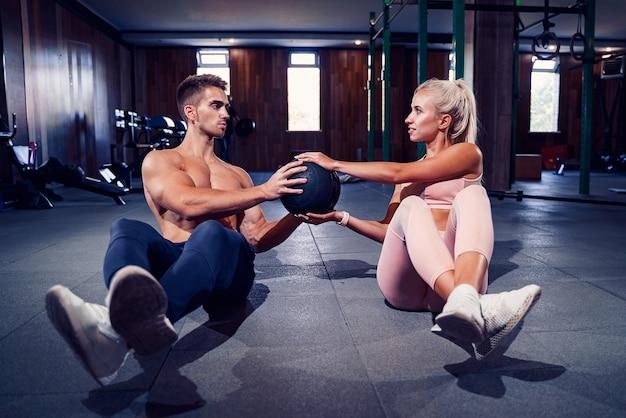 Fit paar buik bal oefening op sportschool doet.