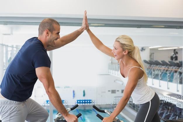 Fit paar geven hoge vijf tijdens het werken op hometrainers op sportschool