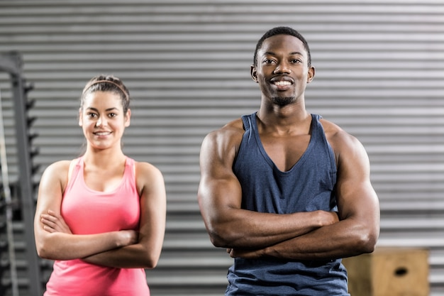 Fit paar met arm gekruist op crossfit sportschool