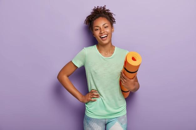 Fit positieve afro vrouw doet fitness oefeningen en training thuis, houdt oranje karemat